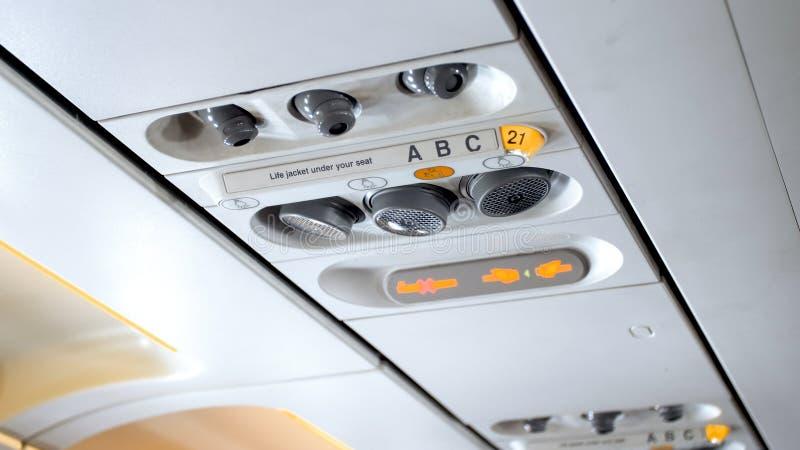 Closeupfoto av knappar och ljus på taket ovanför pasengerplatsen i flygplan royaltyfri fotografi