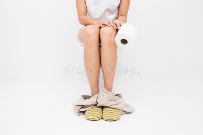 Closeupfoto av kvinnasammanträde på toalett och att använda toalettpapper fotografering för bildbyråer
