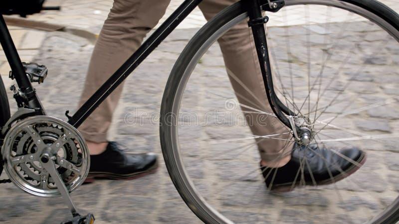Closeupfoto av manlig fot bredvid tappningcykeln på den stenlade vägen royaltyfri fotografi
