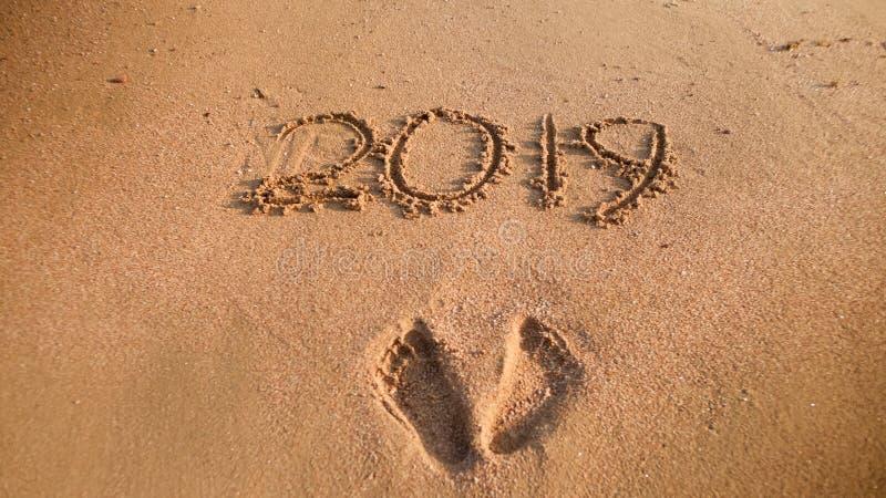 Closeupfoto av 2019 nummer och footrpints för nytt år på våt sand på havstranden Begrepp av det nya året, jul och royaltyfri fotografi
