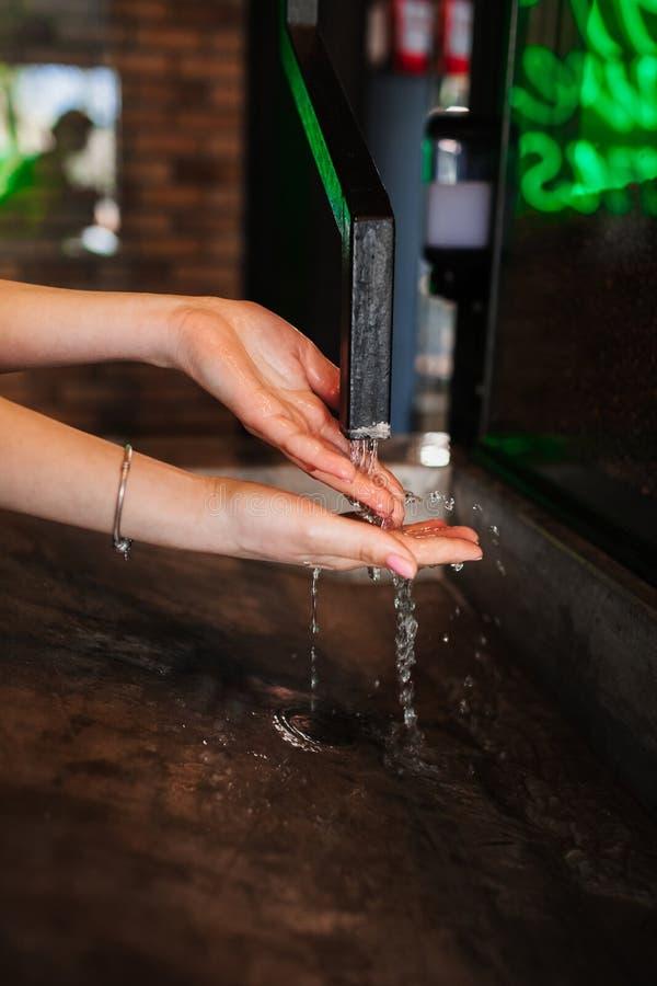 Closeupfoto av tvättande händer för kvinna i kafé vattenflöden i händerna vatten från rör royaltyfria foton