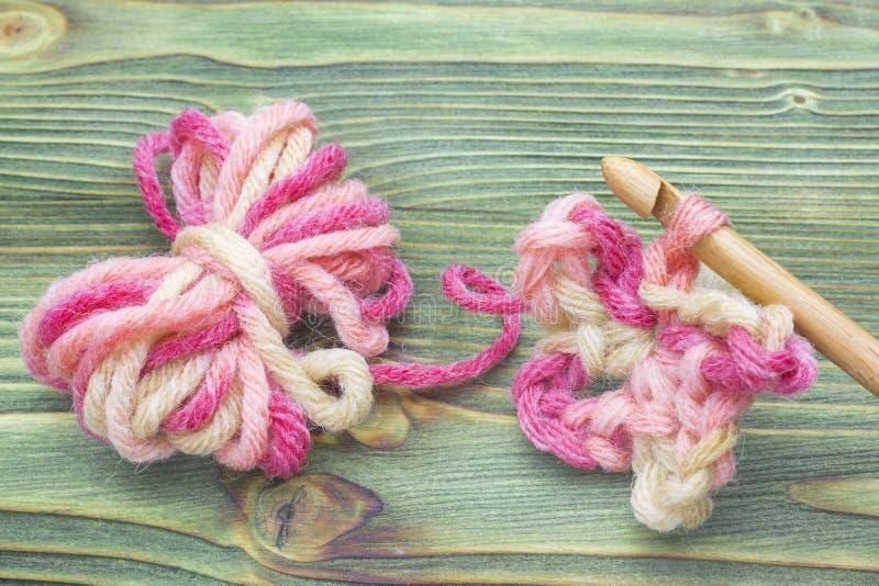 Closeupfoto av virkninghalsduken Varm boll för rosa färgvintergarn för att sticka och virkning på tabellen Lantlig virkningtråd o royaltyfri bild
