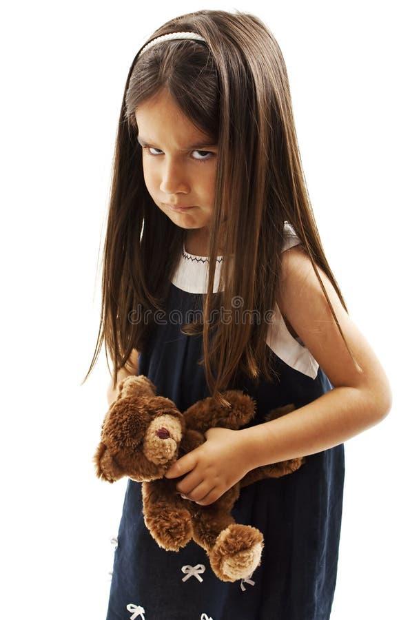Closeupfotoet av lilla flickan visar att hennes fårade krön och irriterat rynka pannan fotografering för bildbyråer