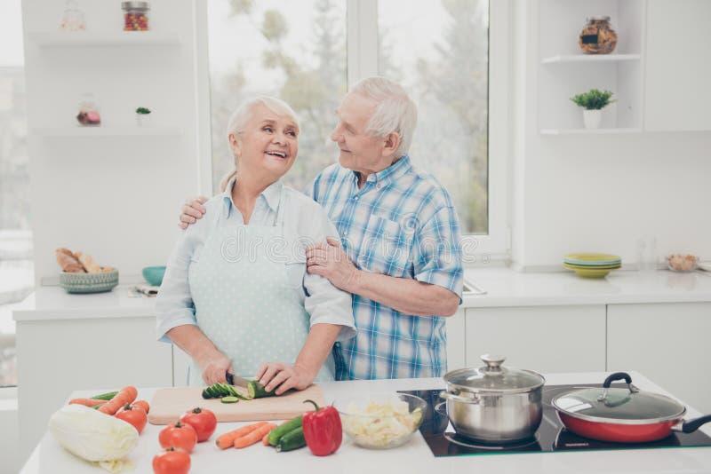 Closeupfotoet av två gulliga par för roligt åldrigt folk förbereder kök för barn för väntan för mötet för familjmatställeårsdagen arkivfoton