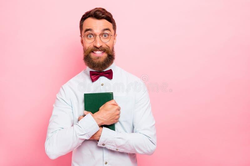 Closeupfotostående av den roliga skraj komiska charmiga grabben med det toothy leendet som omfamnar boken med den gröna räkningen royaltyfri fotografi
