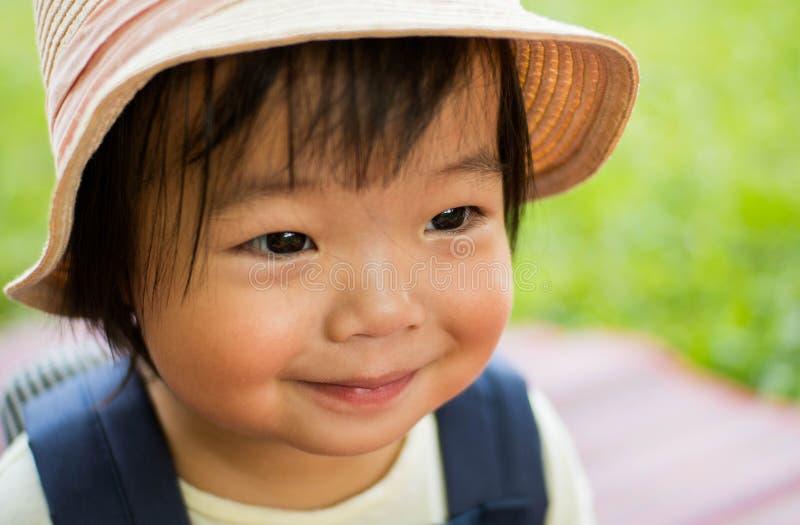Closeupframsida av lyckligt le för liten flicka, det förtjusande barnet som ut ser med härliga blåtiror, och den lyckliga framsid arkivbilder