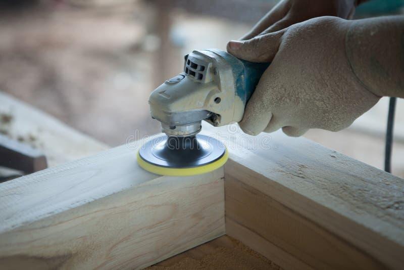 Closeuphänder av snickaren som använder en wood slipmaskin för makthjälpmedel i wor arkivbild
