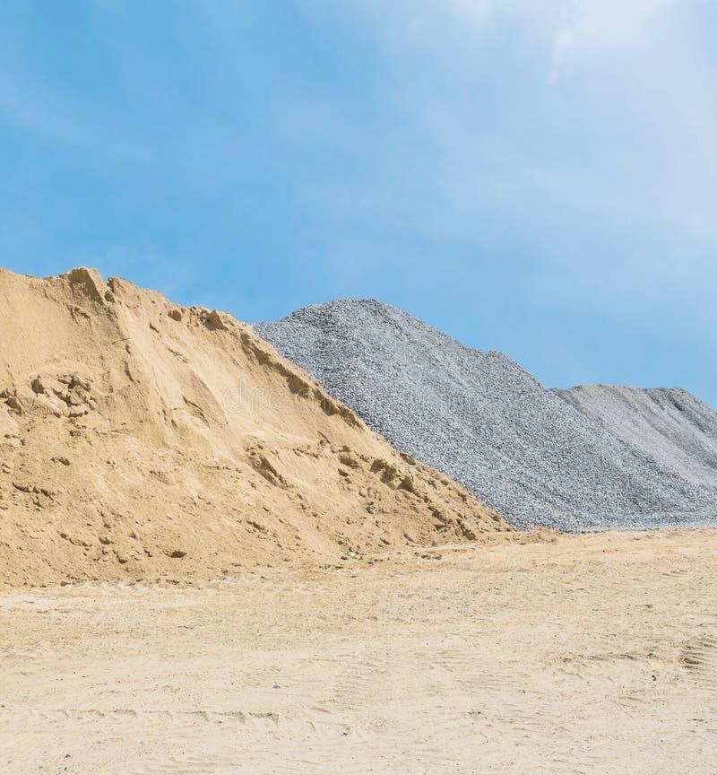 Closeuphögen av sand och stenen för byggnation med jord och blå himmel texturerade bakgrund arkivfoton