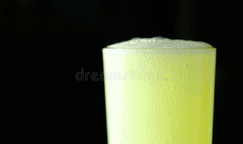 Closeuphalva av fullt exponeringsglas med den kolsyrade gula drinken med skum på en svart bakgrund fotografering för bildbyråer