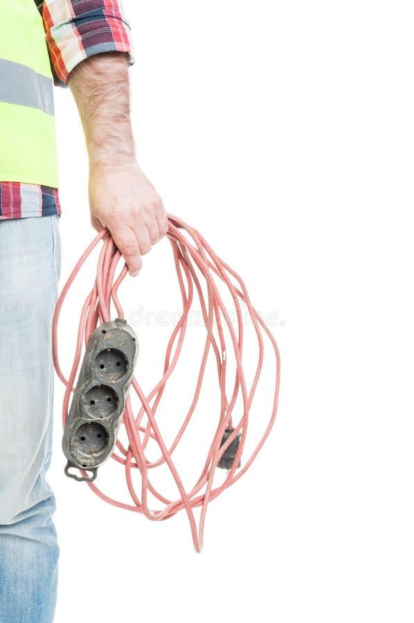 Closeuphand av kabel för förlängning för elektrikerbyggmästare hållande arkivbild