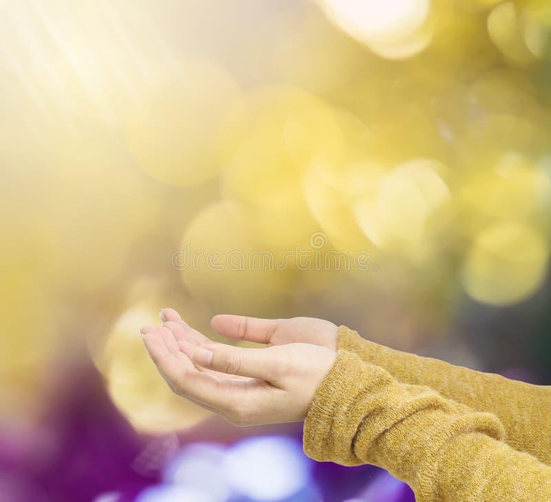 Closeuphandling av kvinnan rymmer ut handen för att vänta bra saker på abstrakt suddig färgrik texturerad bakgrund för ljus fläck royaltyfri bild