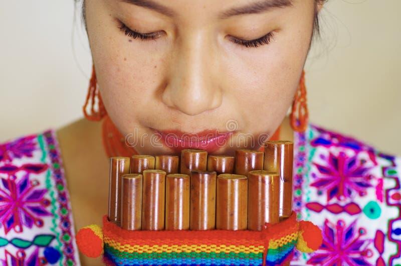 Closeupheadshot av den unga nätta kvinnan som ner bär härliga traditionella andean kläder, sammanträde med, medan spela royaltyfria bilder
