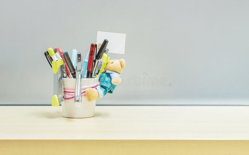 Closeupkontorsutrustning och färgpennan i den rumsrena koppen för skrivbordet för penna på det suddiga träskrivbordet och den fro royaltyfri foto