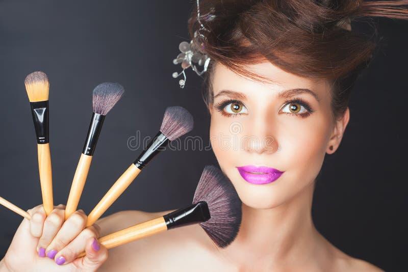 Closeupkvinna på skönhetsalongen Modesmink, utsmyckad frisyr fotografering för bildbyråer