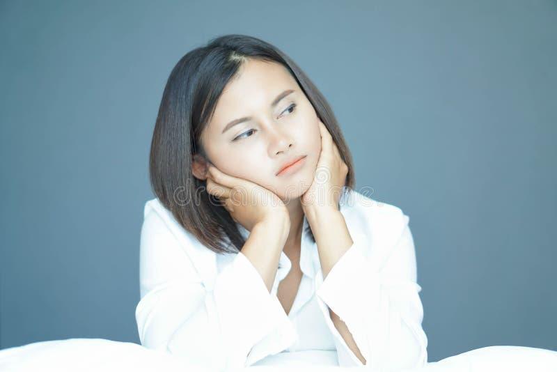 Closeupkvinna som sitter på säng i sovrummet med att tänka eller deprimerad känsla, selektiv fokus royaltyfri bild