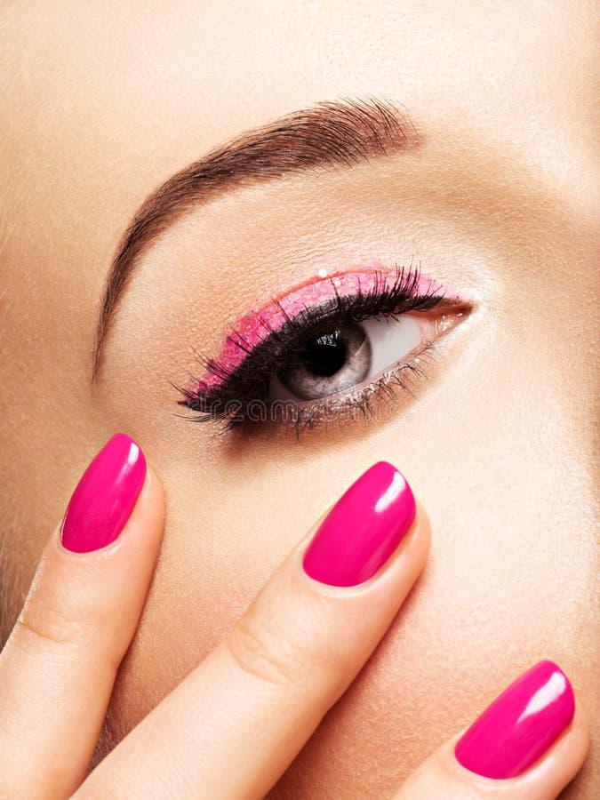 Closeupkvinnaframsidan med rosa färger spikar nära ögon royaltyfri fotografi