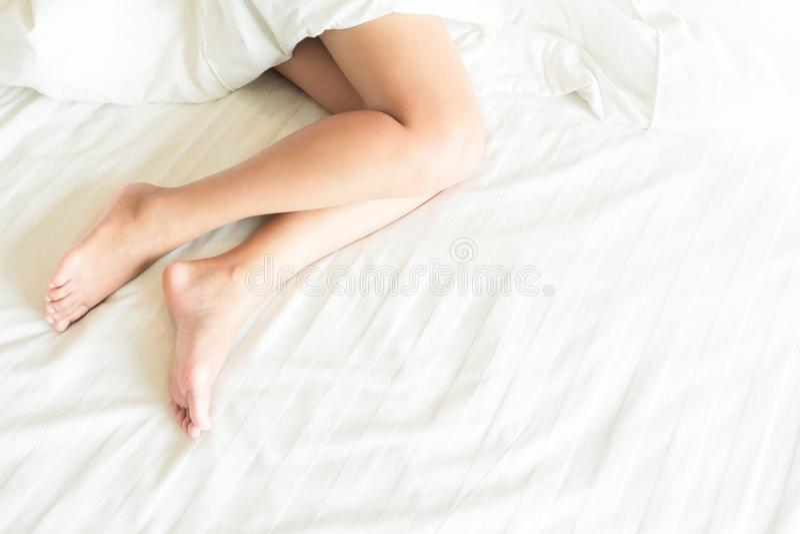 Closeupkvinnan lägger benen på ryggen med att sova på vit säng, skönhet och hud c fotografering för bildbyråer