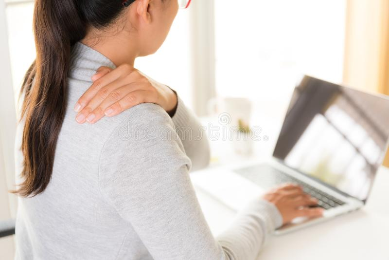 Closeupkvinnan med händer som rymmer hennes skuldra, smärtar Kontorssyndr royaltyfria bilder