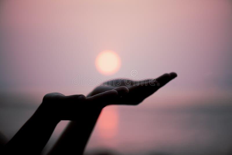 Closeupkvinnan räcker att be för att välsigna från gud under solnedgång royaltyfri fotografi