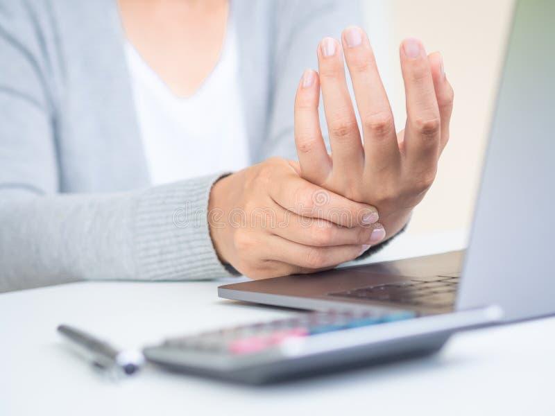 Closeupkvinnan som rymmer hennes hand, smärtar från att använda datoren länge tim royaltyfria foton