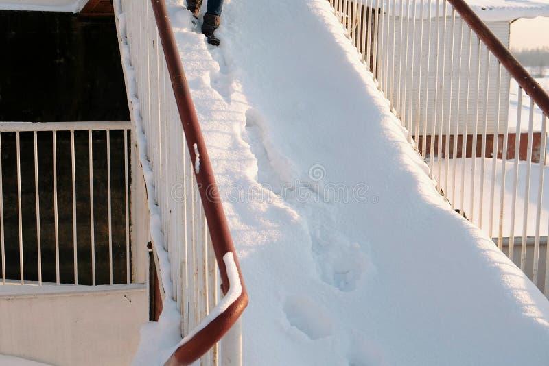 Closeupkvinnans ben får ner en snöig trappuppgång arkivfoto