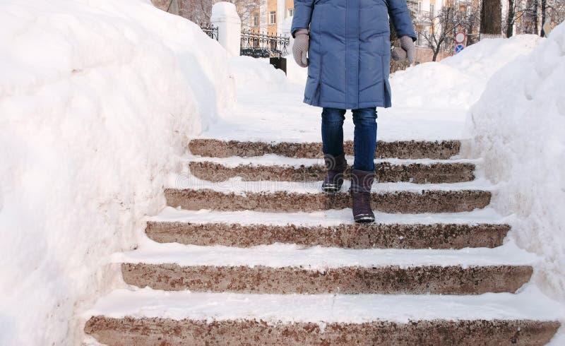 Closeupkvinnans ben går ner på en snöig stege, trappuppgång Vintern parkerar i staden under dagen i snöig väder fotografering för bildbyråer