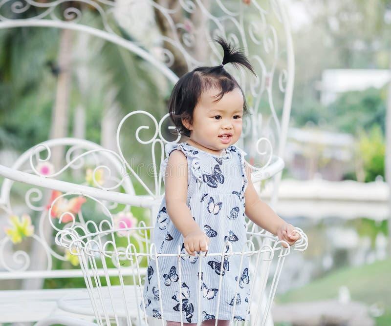 Closeupliten flickaställningen på stålcykelkorgen för dekorerar i trädgårdbakgrunden med leendeframsidan arkivfoto