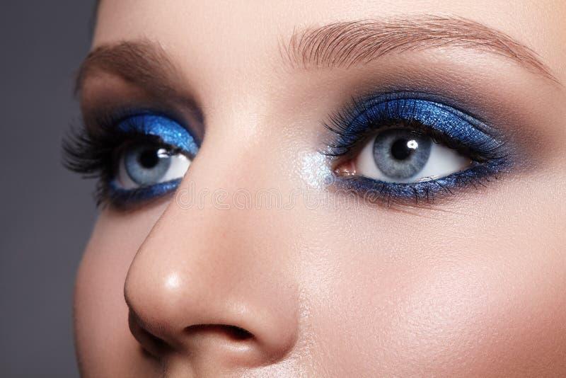 Closeupmakro av kvinnaframsidan med smink för blåa ögon Mode firar makeup, Glowy ren hud, perfekta former av krön royaltyfri foto