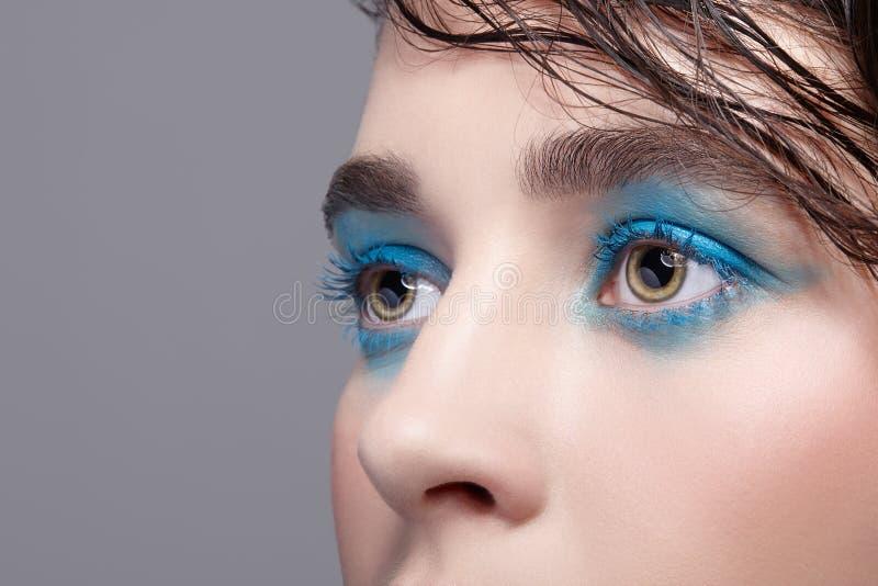 Closeupmakrostående av den kvinnliga framsidan Kvinna med ovanlig skönhetmakeup och vått hår och blått skuggasmink royaltyfria bilder
