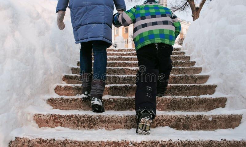Closeupmamma- och sons ben som stiger upp på en snöig stege, trappuppgång Vinterstaden parkerar i snöig dag med fallande snö royaltyfria bilder