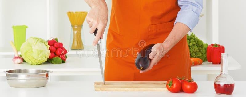 Closeupman` s räcker bitande grönsaker på en arbetsyttersida i ett kök Sund livsstil casserole som lagar mat läckert home hemlaga arkivfoto