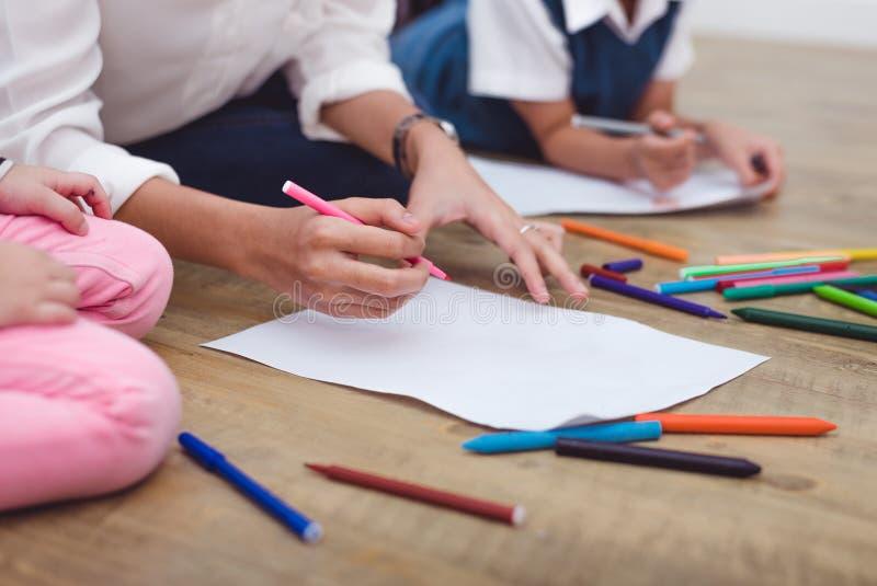 Closeupmoder och små barn som drar tecknade filmen i konstgrupp till att dra tecknade filmen i konstgrupp med färgblyertspennan t royaltyfri fotografi