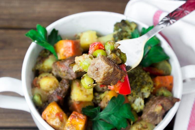 Closeupnötköttkött lät småkoka med grönsaker i keramisk kruka med ett stycke på en gaffel på träbakgrund royaltyfri bild