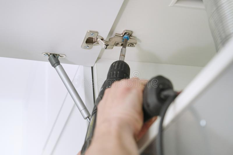 Closeupprocess av att montera kökmöblemang, händer av den manliga arbetaren med yrkesmässiga hjälpmedel royaltyfri bild