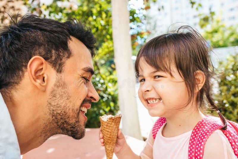 Closeupsidosikt av den lyckliga gulliga lilla flickan som sitter med den stiliga farsan som utomhus äter glass Rolig flickaunge o arkivfoto