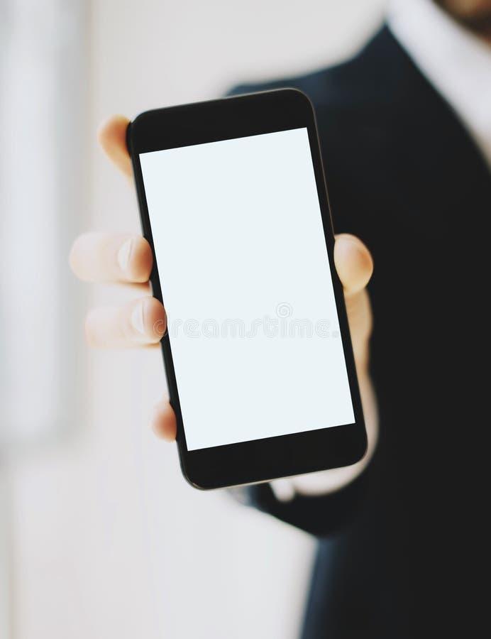 Closeupsikt av affärsmannen i en svart dräktvisningsmartphone med vit skärm för lodlinjemellanrum Tom modell som är suddig royaltyfria bilder