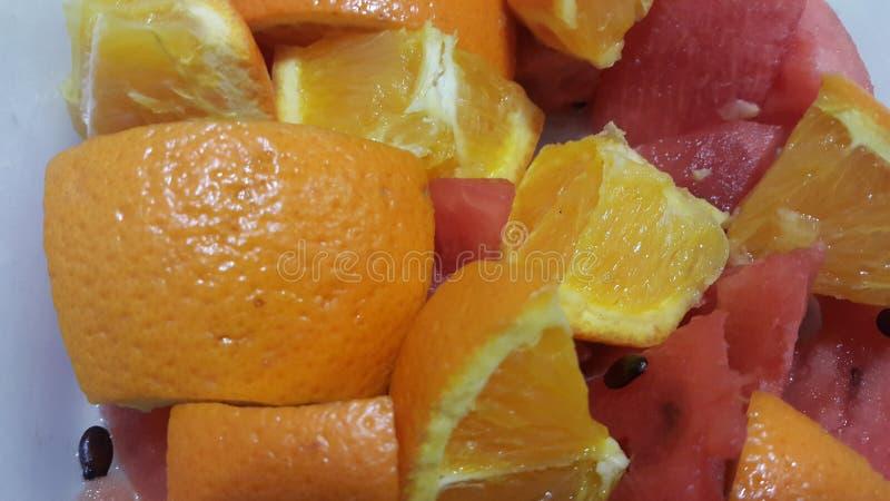 Closeupsikt av blandade fruktskivor av citrusa apelsiner och den söta röda vattenmelon royaltyfria foton