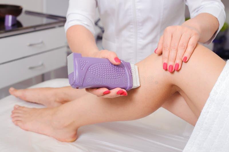 Closeupsikt av cosmetologisten i gummihandskar som applicerar vaxet på benet arkivbild