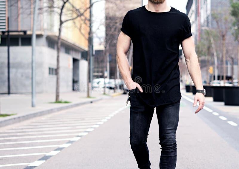 Closeupsikt av den unga muskulösa mannen som bär den svarta tshirten och jeans som går på gatorna av den moderna staden _ royaltyfri fotografi