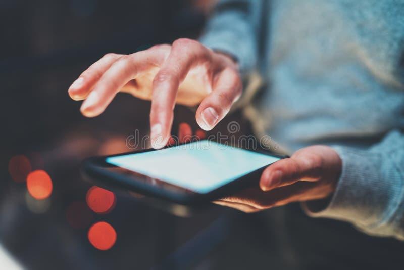 Closeupsikt av flickan som rymmer den moderna smartphonen i händer Flickamaskinskrivning på den mobila skärmen för vitt handlag p arkivbild