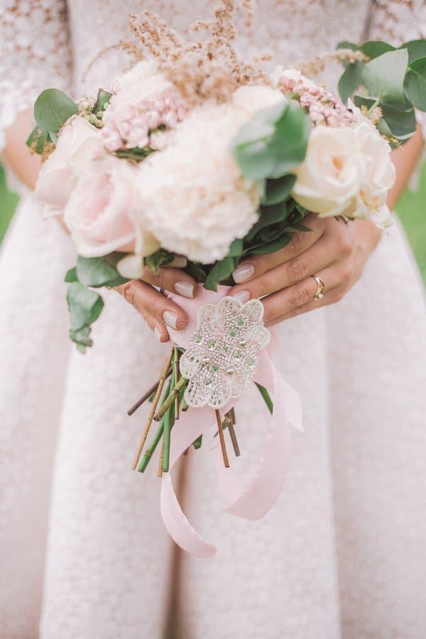 Closeupsikt av härliga brud- händer som rymmer den perfekta brud- buketten royaltyfri fotografi