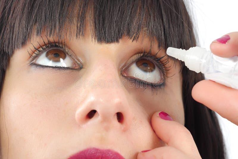 Closeupsikt av kvinnan som applicerar ögondroppe royaltyfri foto
