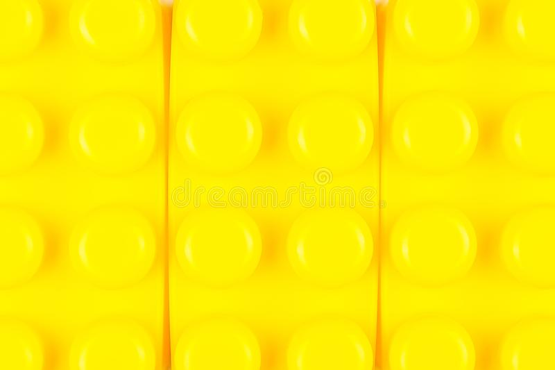 Closeupsikt av plast- byggandekvarter Gul bakgrund royaltyfria foton