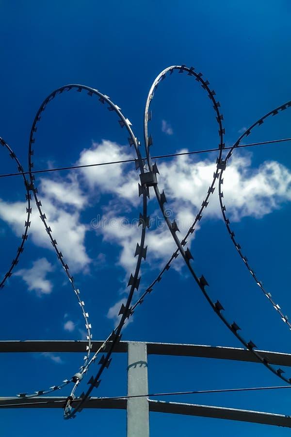 Closeupsikt av taggtrådstaketet som bildar en form av hjärta på blå bakgrund för molnig himmel Andataggtråd Symbolfaravarning royaltyfria foton