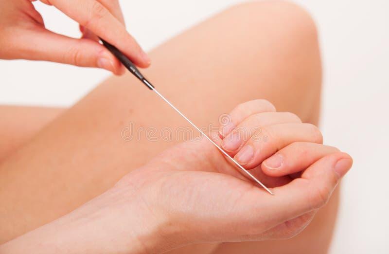 CLoseupsikten av att använda för manicurebehandling spikar mappen arkivfoto