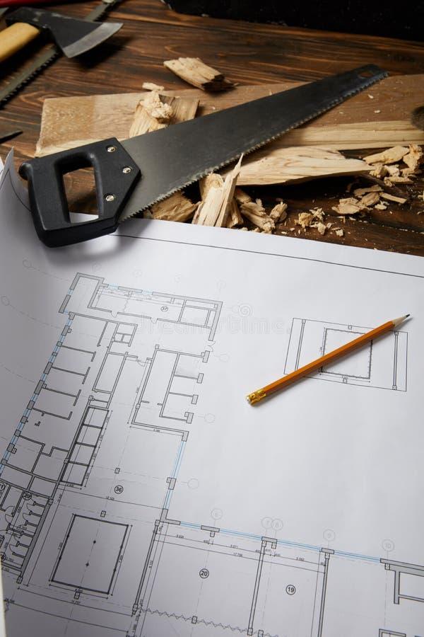 closeupsikten av den arkitektoniska ritningen, blyertspennan, handsawen, yxan och att klara av såg på trätabellen royaltyfria foton