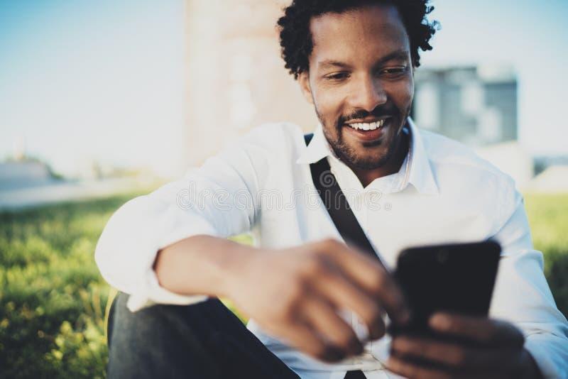 Closeupsikten av den unga le afrikanska mannen som överför peka fingret på smartphonen, medan sitta på den soliga staden, parkera arkivfoton