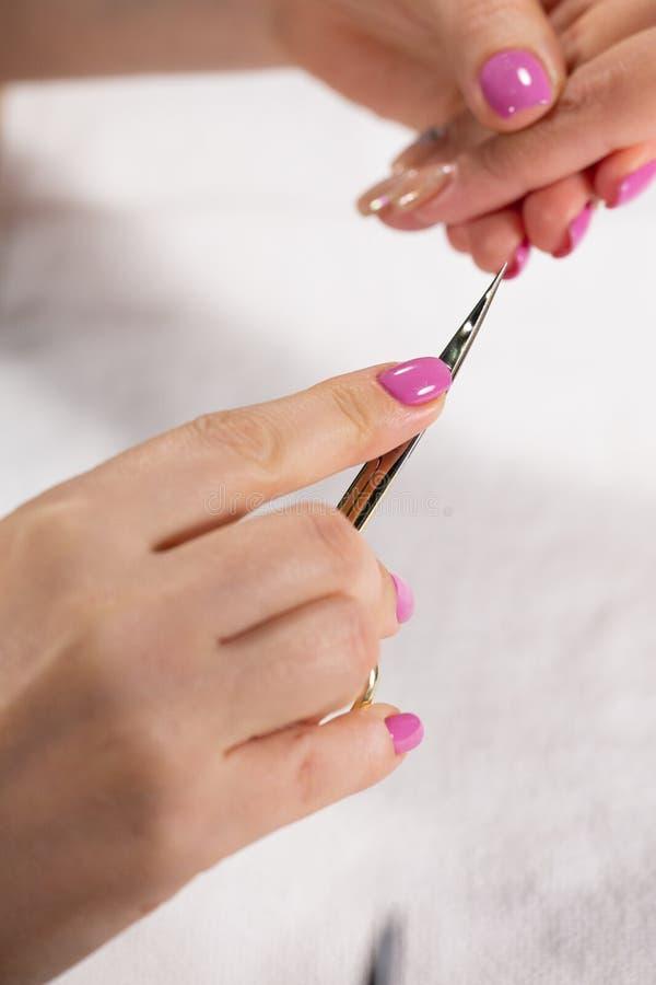 Closeupsikten av händer med manikyr av den unga kvinnan spikar behandling av en specialist i salongen royaltyfri foto