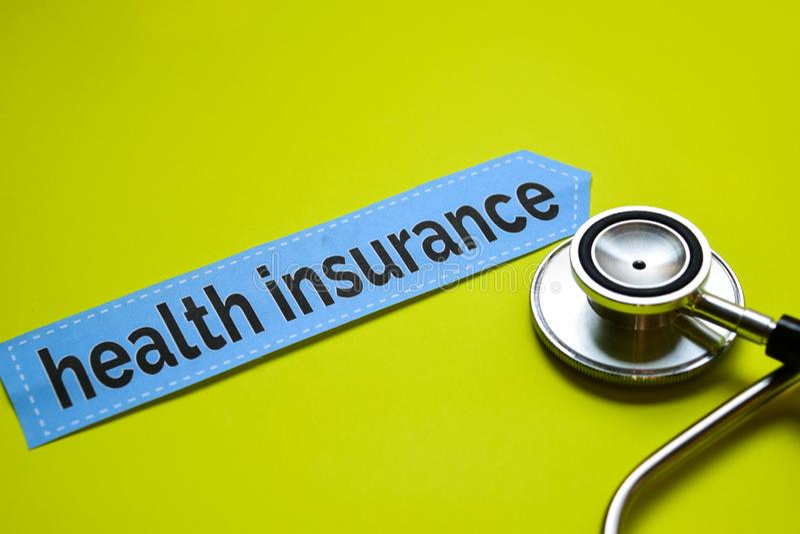 Closeupsjukförsäkring med stetoskopbegreppsinspiration på gul bakgrund arkivbild