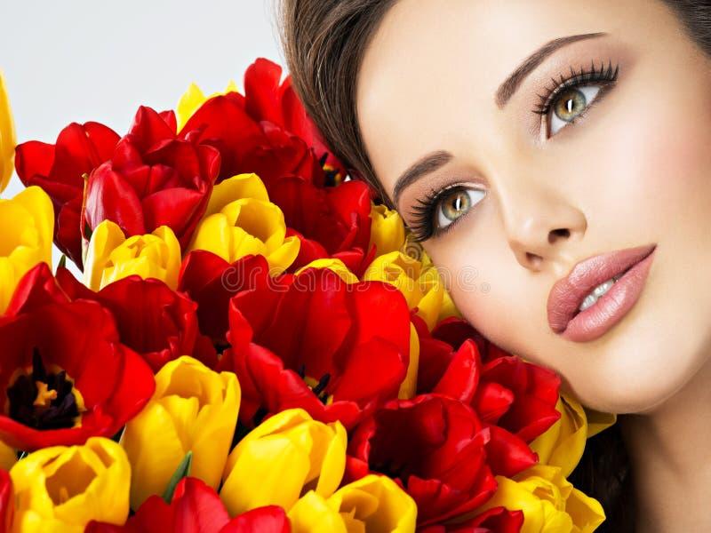Closeupskönhetframsida av den unga kvinnan med blommor royaltyfria foton